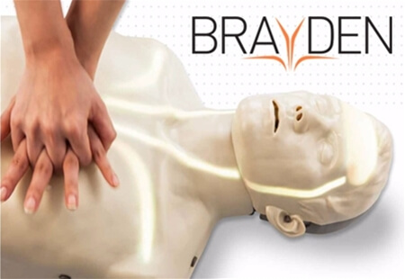 View of two hands performing CPR on a Brayden Manikin with the Brayden logo in the top right of the image.