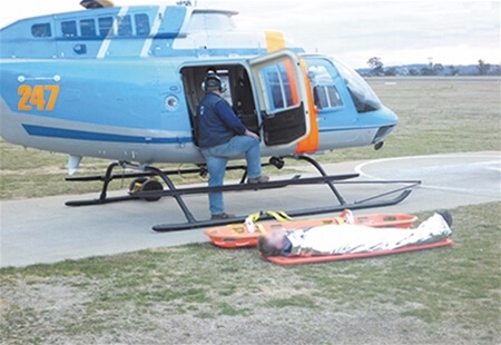 View of an individual on a Stretcher waiting to be lifted into a parked helicopter.