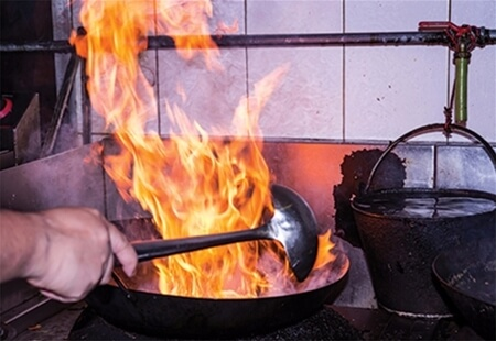 View of an individual cooking with a large pan that is producing large flames.