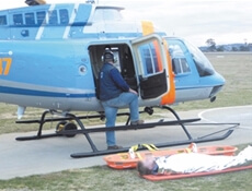 Image displaying a patient secured to a stretcher next to a parked up emergency helicopter.