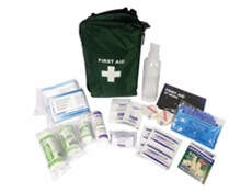 View of a travel first aid kit bag with all of its included contents emptied out in front of it.